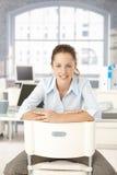 Mulher nova que senta-se no sorriso do escritório imagem de stock royalty free
