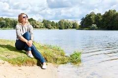 Mulher nova que senta-se perto da água Imagens de Stock