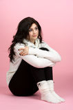 Mulher nova que senta-se sobre a cor-de-rosa Foto de Stock