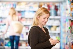 Mulher nova que sorri ao comprar Fotografia de Stock