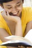 Mulher nova que sorri ao ler Fotografia de Stock Royalty Free