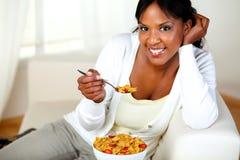 Mulher nova que sorri em você e que come o pequeno almoço Imagens de Stock