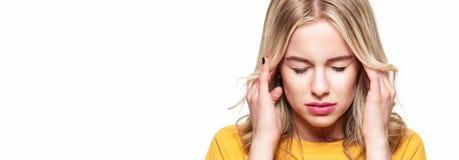 Mulher nova que tem a dor de cabeça Jovem mulher esgotada forçada que faz massagens seus templos Mulher que sofre da enxaqueca foto de stock royalty free