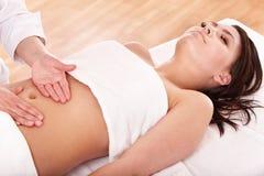 Mulher nova que tem a massagem do estômago. Foto de Stock Royalty Free