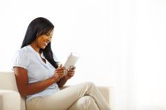 Mulher nova que tem o divertimento com um PC da tabuleta Imagens de Stock