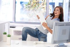 Mulher nova que tem o divertimento no escritório brilhante