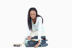 Mulher nova que tem problemas fechar sua mala de viagem Imagens de Stock Royalty Free