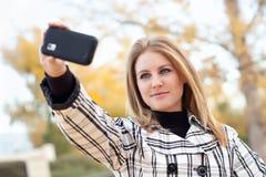 Mulher nova que toma o retrato com telefone da câmera Imagem de Stock