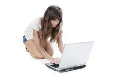 Mulher nova que trabalha com portátil foto de stock