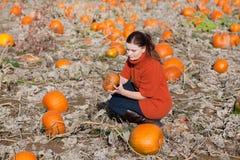 Mulher nova que trabalha no campo da abóbora Imagens de Stock