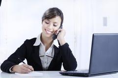 Mulher nova que trabalha no escritório com telefone Fotografia de Stock Royalty Free