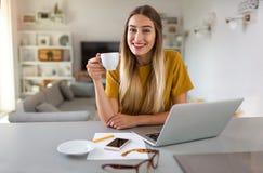 Mulher nova que trabalha no portátil em casa imagens de stock