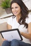 Mulher nova que usa o computador da tabuleta em casa Fotografia de Stock