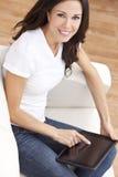 Mulher nova que usa o computador da tabuleta em casa Fotos de Stock
