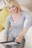Mulher nova que usa o computador da tabuleta em casa no sofá Fotos de Stock Royalty Free