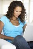 Mulher nova que usa o computador portátil em casa Fotografia de Stock