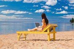Mulher nova que usa o portátil Foto de Stock