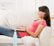Mulher nova que usa o portátil no sofá em casa Fotografia de Stock