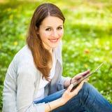 Mulher nova que usa seu computador da tabuleta Fotos de Stock