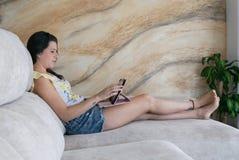 Mulher nova que usa um computador da tabuleta foto de stock royalty free
