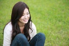 Mulher nova relaxada em um gramado Fotografia de Stock