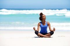 Mulher nova saudável da ioga que medita na praia imagem de stock royalty free