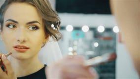Mulher nova sensual que aplica cosméticos em seus bordos filme