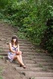 A mulher nova senta no escadas Fotografia de Stock