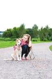 A mulher nova senta-se com o filhote de cachorro ao ar livre Imagem de Stock