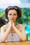 A mulher nova senta-se em pouca tabela Fotos de Stock Royalty Free