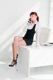 A mulher nova senta-se em uma tabela no escritório foto de stock royalty free