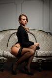 A mulher nova senta-se no sofá Imagem de Stock