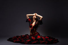 A mulher nova senta-se no traje preto e vermelho aciganado Imagem de Stock