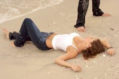Mulher nova 'sexy' bonita em calças de brim molhadas na praia Fotos de Stock Royalty Free