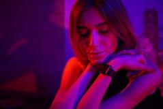 Mulher nova 'sexy' da beleza que levanta sobre o fundo de néon vermelho da cidade da noite e azul dramático fotos de stock royalty free
