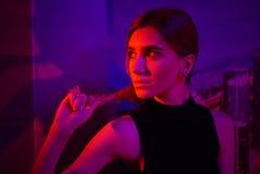 Mulher nova 'sexy' da beleza que levanta sobre o fundo de néon vermelho da cidade da noite e azul dramático imagens de stock royalty free