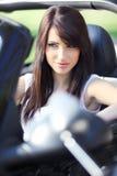 Mulher nova 'sexy' que conduz o carro preto. Imagens de Stock