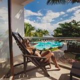 Mulher nova 'sexy' que relaxa na cadeira de plataforma Fotografia de Stock Royalty Free