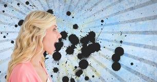 Mulher nova surpreendida do estudante que está contra o fundo chapinhado azul Foto de Stock Royalty Free
