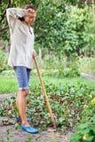 Mulher nova Tired com o hoe que trabalha no jardim imagem de stock royalty free