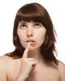 A mulher nova tocou em seu dedo a seus bordos. Imagens de Stock Royalty Free
