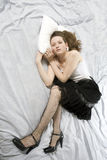 Mulher nova triste que encontra-se para baixo na cama Fotos de Stock Royalty Free