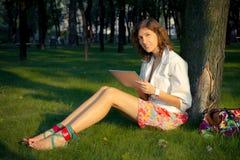 A mulher nova usa o PC da tabuleta no parque imagem de stock royalty free