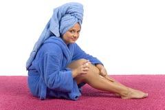 A mulher nova vestiu o creme azul da fricção do bathrobe em seu pé imagem de stock