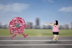 Mulher obeso perseguida pela filhós saboroso Foto de Stock