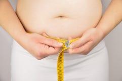 Mulher obeso que mede sua cintura com uma fita de medição Foto de Stock