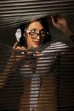 A mulher observa a espreitadela no jalousie imagem de stock
