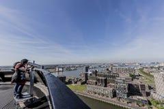 Mulher observando através de um telescópio a cidade de Rotterdam imagens de stock royalty free