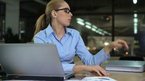 A mulher obtém mais documento no fim do dia de trabalho, fechando o dobrador para evitar o trabalho video estoque