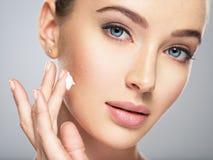 A mulher obtém o creme na cara Conceito do cuidado de pele foto de stock